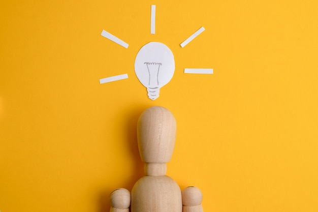 Het concept van een gevonden bedrijfsidee of startup. houten mannequin op een gele achtergrond onder een geschilderde gloeilamp.