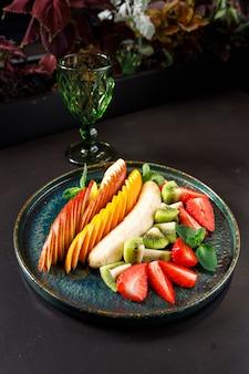 Het concept van een gezond dieet. schotel fruit en bessen - appel, sinaasappel, banaan, kiwi, aardbei, munt