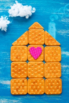 Het concept van een koekjeshuis op een houten blauwe hemelwolk