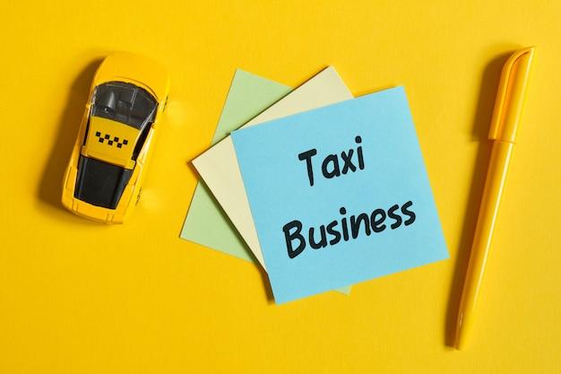 Het concept van een taxi als bedrijf. speelgoedauto op een gele muur met een sticker. bovenaanzicht.