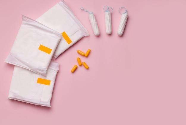 Het concept van een vertraagde menstruatiecyclus bij vrouwen. pads met tampons en pillen.