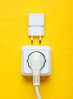 Het concept van elektrische afhankelijkheid. de stekker is aangesloten op het stopcontact en de oplader. bovenaanzicht
