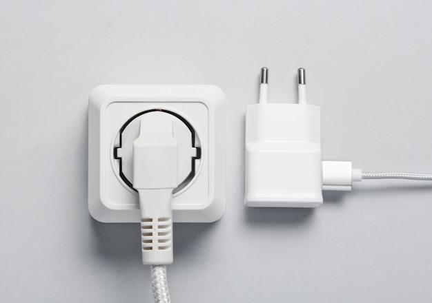 Het concept van elektrische afhankelijkheid. de stekker zit in het stopcontact en de oplader. bovenaanzicht
