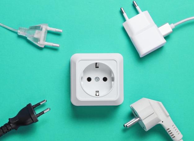 Het concept van elektrische afhankelijkheid. veel stekkers bij stopcontacten op blauwe achtergrond