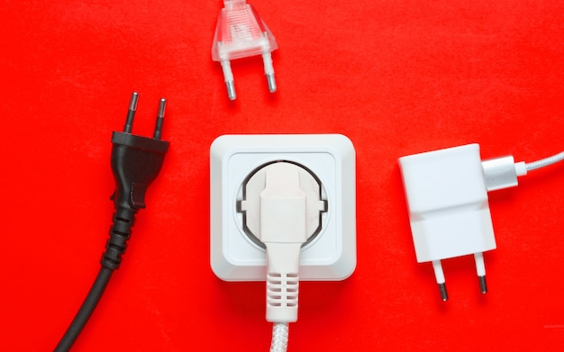 Het concept van elektrische afhankelijkheid. veel stekkers bij stopcontacten op rode achtergrond