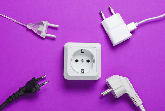 Het concept van elektrische afhankelijkheid. veel stekkers in de buurt van stopcontacten op paarse tafel