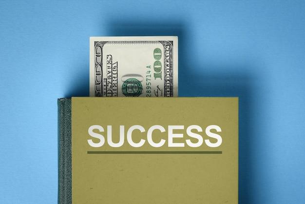 Het concept van financieel succes. een boek met antwoorden op de vraag: hoe geld verdienen en beleggen. dollarbiljet tussen boekpagina's (bladwijzer)
