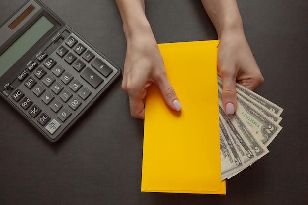 Het concept van financieel welzijn, het meisje in haar hand houdt een gele envelop met geld.