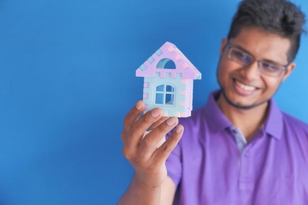 Het concept van financiën concept gelukkig jonge man huis in de hand te houden