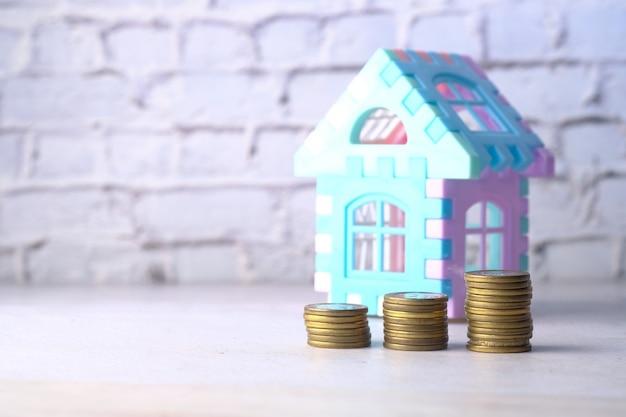Het concept van financiën concept met stapel munten en huis op tafel.