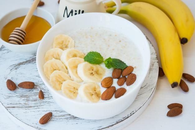 Het concept van goede voeding. gezond ontbijt van havermout met banaan en noten in een witte plaat op een witte muur. horizontale oriëntatie. detailopname