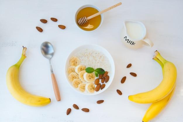 Het concept van goede voeding. gezond ontbijt van havermout met banaan, honing en noten in een witte plaat in het midden van de tabel op een witte muur. horizontale oriëntatie. bovenaanzicht.