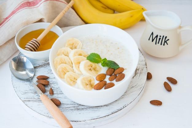 Het concept van goede voeding. gezond ontbijt van havermout met banaan, honing en noten in een witte plaat op een witte muur. horizontale oriëntatie.