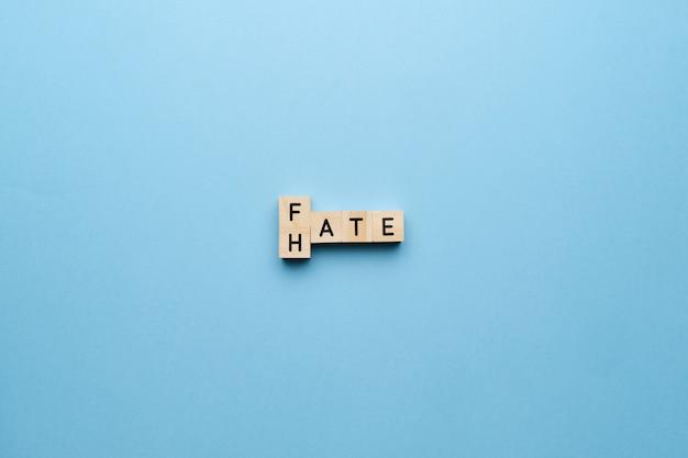 Het concept van haat en lot. letters op een blauwe achtergrond.