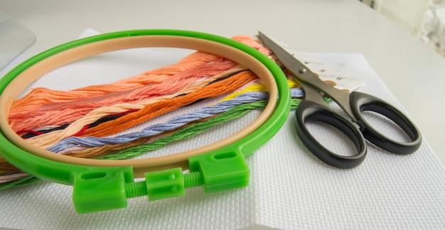 Het concept van handwerken. naaibenodigdheden voor borduurwerk-canvas, hoepel, draadzijde