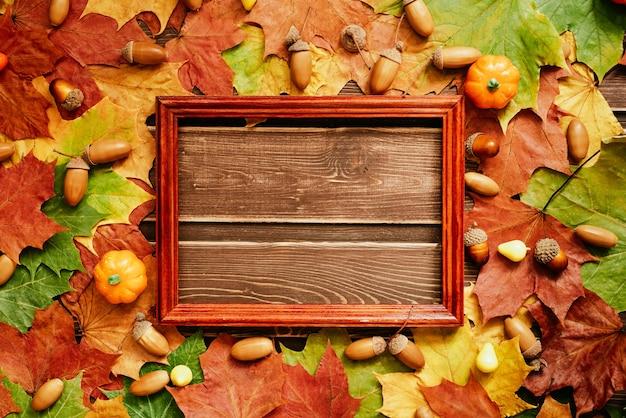 Het concept van herfstbehang. gedroogde esdoornbladeren en eikels bekleed met een frame met een kopieerruimte voor uw tekst