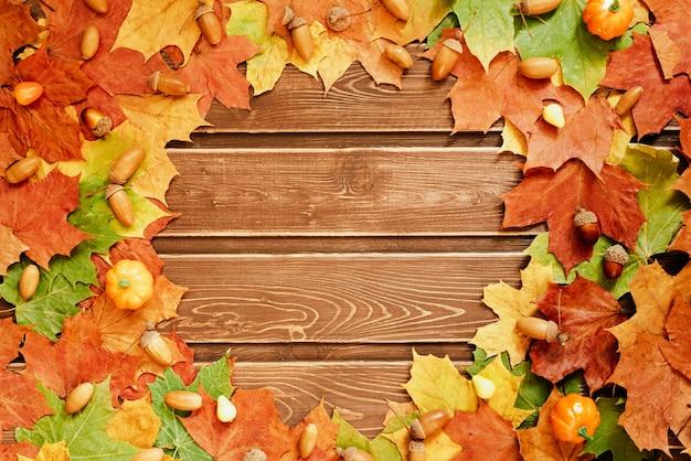 Het concept van herfstbehang. gedroogde esdoornbladeren en eikels bekleed met een rond frame met een kopieerruimte voor uw tekst