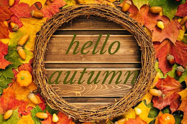 Het concept van herfstbehang. gedroogde esdoornbladeren en eikels bekleed met een rond frame met tekst: hallo herfst.