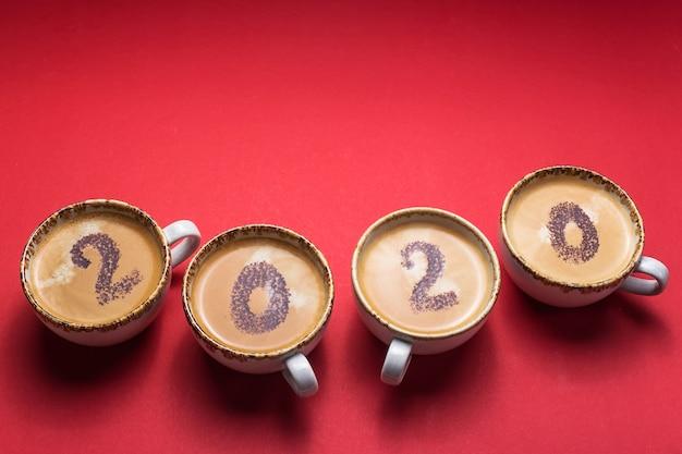 Het concept van het begin van de nieuwe 2020 is getekend op kopjes koffie