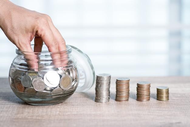 Het concept van het besparingsgeld voorafgesteld door mannelijke hand die de stapel groeiende zaken van het geldmuntstuk zetten