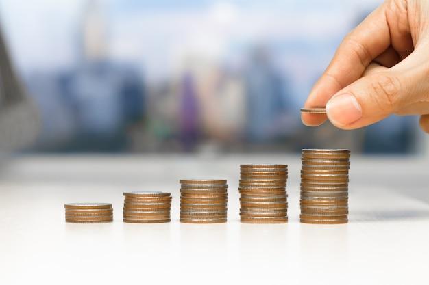 Het concept van het besparingsgeld voorafgesteld door mannelijke hand die de stapel groeiende zaken van het geldmuntstuk zetten.