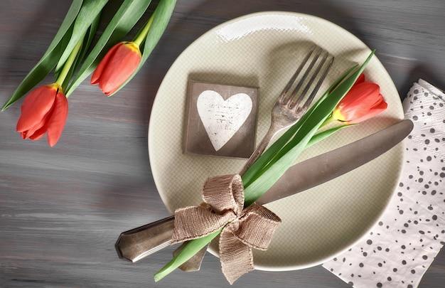 Het concept van het de lentemenu met verse tulpen en hartdecoratie op hout