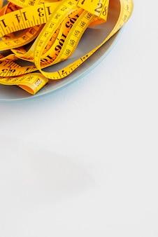Het concept van het dieet. de vork teruggewonden centimeter die op plaatclose-up ligt