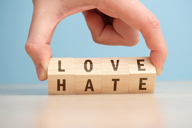 Het concept van het kiezen tussen liefde en haat op houten kubussen wordt met de hand omgedraaid.