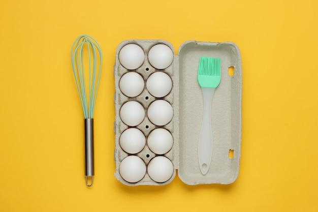 Het concept van het koken het kartonnen dienblad van eierenkeukengereedschap zwaait borstel op gele achtergrond