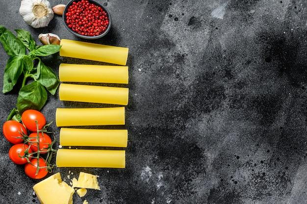 Het concept van het koken van cannelloni pasta. ingrediënten basilicum, kerstomaatjes, parmezaan, knoflook. zwarte achtergrond. bovenaanzicht. kopieer ruimte