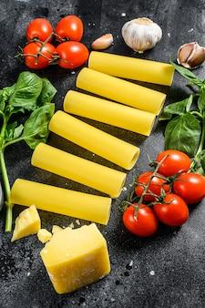Het concept van het koken van cannelloni pasta. ingrediënten basilicum, kerstomaatjes, parmezaan, knoflook. zwarte achtergrond. bovenaanzicht