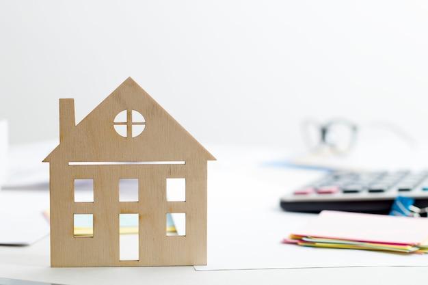 Het concept van het kopen van een huis, hypotheek. huismodel op de desktop makelaar.