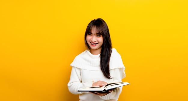 Het concept van het lezen van boeken verhoogt de kennis, verhoogt de concentratie. vrouw die een boek leest leuke aziatische vrouw die gelukkig lacht. op een gele achtergrond