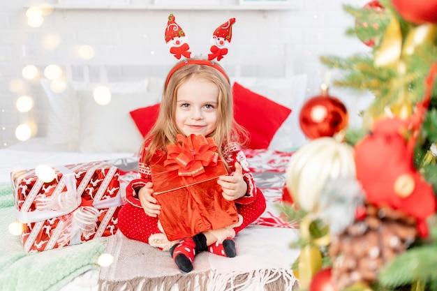 Het concept van het nieuwe jaar en kerstmis, een meisjeskind op het bed thuis met geschenken die wachten op het nieuwe jaar of kerstmis in een rode trui en lachend van geluk