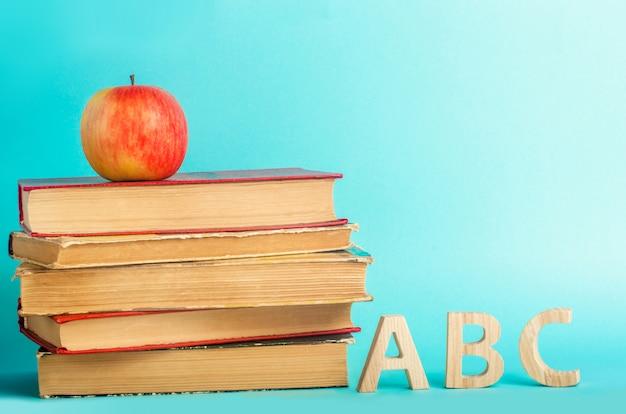 Het concept van het onderwijs. appel, boeken en alphabe, blauwe achtergrond, plaats voor tekst, terug naar school