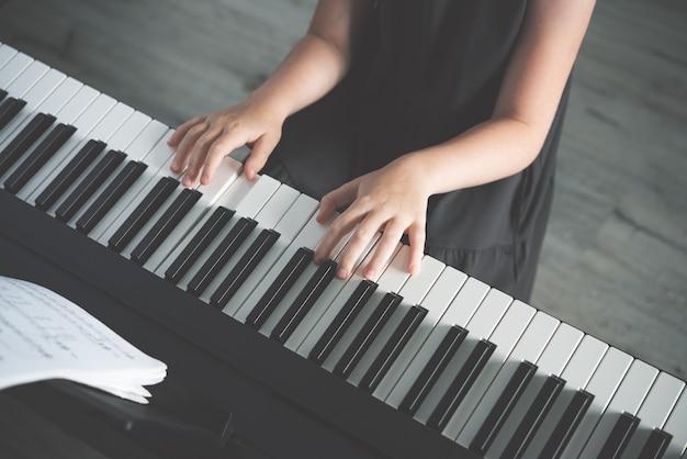 Het concept van het ontwikkelen van kinderactiviteiten. een meisje in een grijze jurk speelt een elektronische piano. zonder gezicht. bovenaanzicht en tintafbeelding