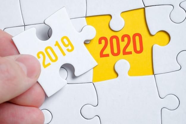 Het concept van het veranderen van het jaar van 2019 naar 2020. een stukje van de puzzel wordt vastgehouden door een man met zijn vingers