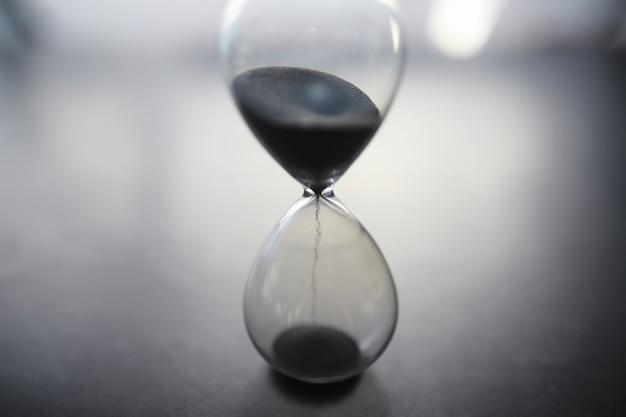 Het concept van het verstrijken van de tijd. zandloper op een donkere achtergrond. inscriptie tijd. de schaduw op het oppervlak van het woord.