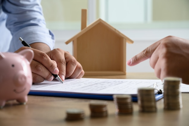 Het concept van huiseigendom zakenmensen onderhandelen over een contract hier moet u tekenen