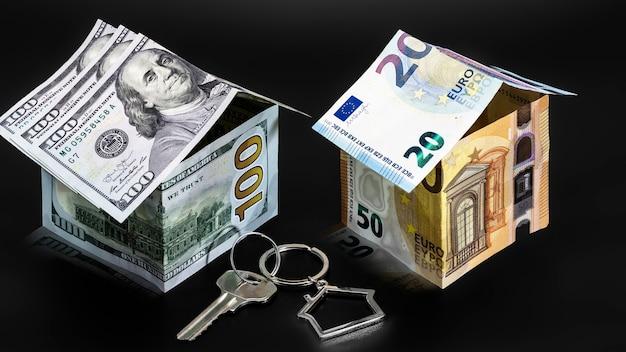 Het concept van hypotheek en huurwoningen en onroerend goed. hypothecaire kredietverlening. een huis kopen. metalen sleutelhanger in de vorm van een huis met een sleutel. huizen gemaakt van dollar en euro biljetten.