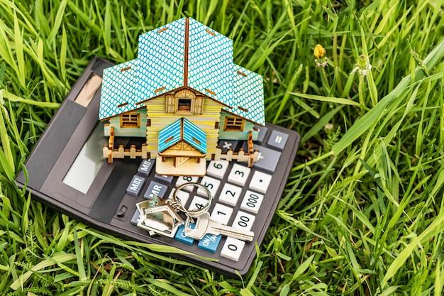 Het concept van hypotheek en huurwoningen en onroerend goed. hypothecaire kredietverlening. huisindeling met een rekenmachine op een bloeiende weide. milieuvriendelijke woningen kopen.