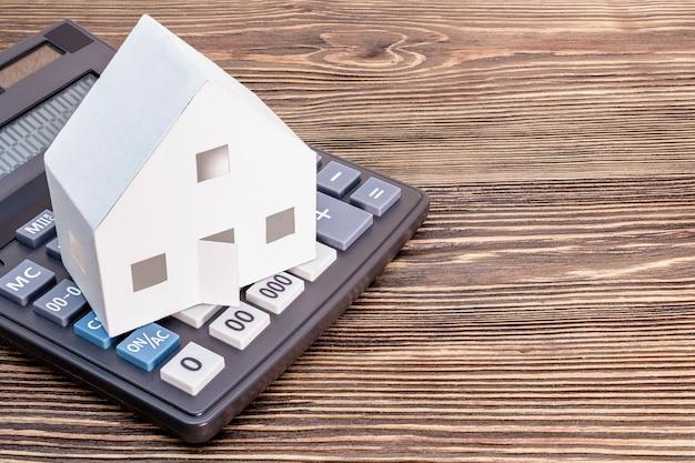 Het concept van hypotheek, verkoop en verhuur van woningen en onroerend goed. hypothecaire kredietverlening. rekenmachine waarop een mock-up staat van een papieren huis op een houten ondergrond. ruimte kopiëren.
