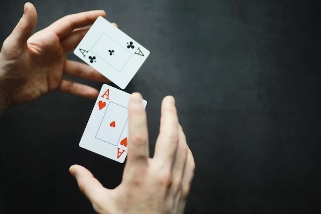 Het concept van kaarttrucs en presentaties. het concept van een sharpie in games. vliegende kaarten in de lucht. een goochelaar heft kaarten op met de kracht van het denken.