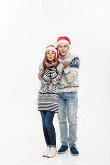 Het concept van kerstmis - van gemiddelde lengte jong aantrekkelijk kaukasisch paar dat een kus geeft die voor eerste kerstdag viert.