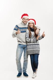 Het concept van kerstmis - van gemiddelde lengte jong aantrekkelijk kaukasisch paar dat een omhelzing geeft die voor eerste kerstdag viert.
