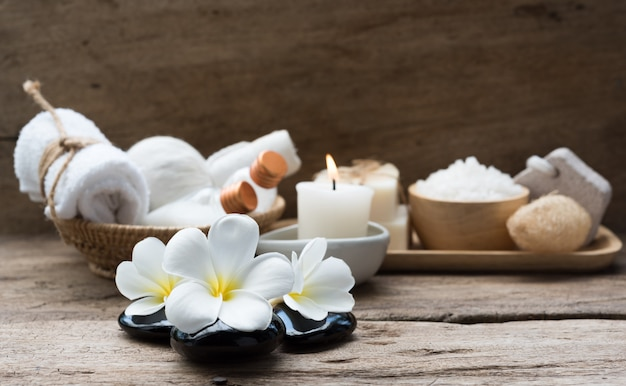 Het concept van kuuroordwellness, witte kaars, melkzeep, zout, handdoek, bloemen en kruidenmassagebal op rustieke houten lijst