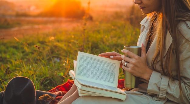 Het concept van levensstijl en familie openluchtrecreatie in de herfst. vrouw met hoed lees boeken over plaid met een thermobeker. herfst. zonsondergang. knus