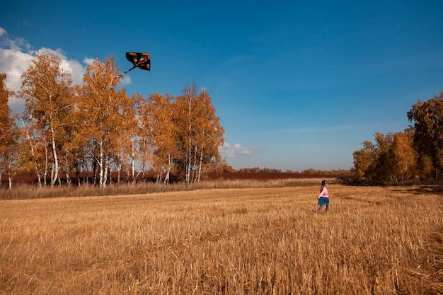 Het concept van livestyle en familie openluchtrecreatie in de herfst. een blond vrolijk meisje geniet van de natuur en speelt met een vlieger op een warme zonnige herfstdag op de achtergrond van een veld en gele bomen.