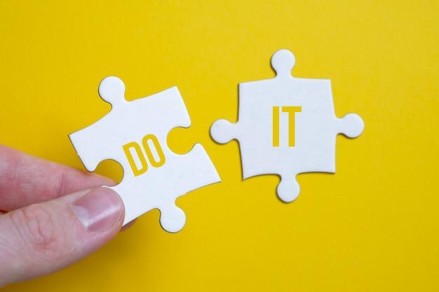 Het concept van motivatie om actie te ondernemen. een stukje van de puzzel met het opschrift houdt met zijn vingers een man naast een ander op een geel oppervlak