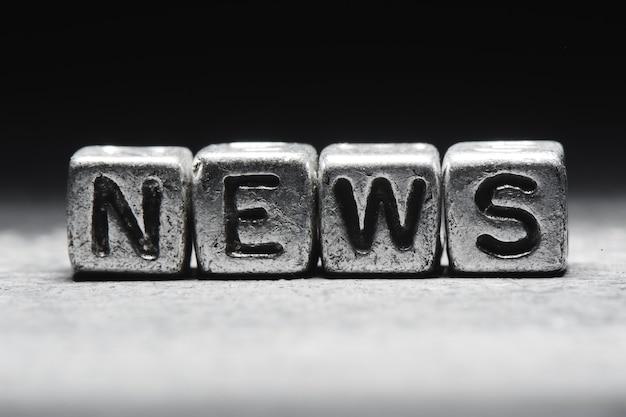 Het concept van nieuws. inschrijving op metalen 3d-kubussen geïsoleerd op een zwarte achtergrond, grunge-stijl